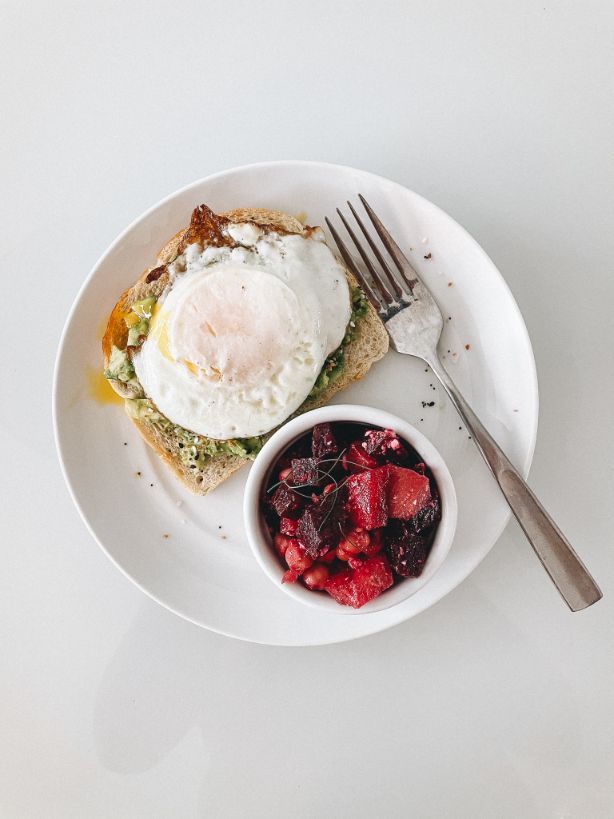 Minimalist Photo White Background Plate with Avocado Toast Topped with Fried Egg and Everything but the Bagel Seasoning. Side Beet Salad in a small bowl on plate